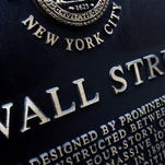 FILE - This Jan. 4, 2010, file photo, shows an historic marker on Wall Street in New York. Japan led global stock markets higher Friday, Jan. 29, 2016, after its central bank introduced a negative interest rate policy in the latest move to overcome malaise in the world's third-biggest economy. The yen dived against the dollar and the euro.