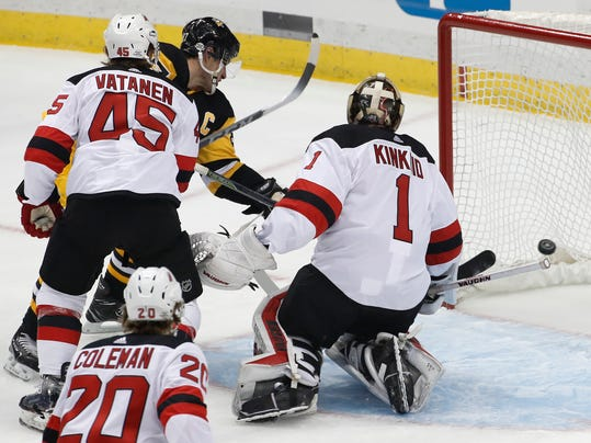 Pittsburgh Penguins' Sidney Crosby (87), rear left, puts a rebound behind New Jersey Devils goaltender Keith Kinkaid (1) with Sami Vatanen (45) defending during the first period of an NHL hockey game in Pittsburgh, Tuesday, Feb. 27, 2018. (AP Photo/Gene J. Puskar)