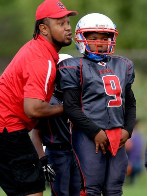 Kappa Express coach Jibreel Goins moves a player into position against the Lansing Warriors in a 7U Lansing Football League game in September at the Southside Community Center in Lansing. Goins suffered a massive seizure during the team's championship game on Oct. 20 and later died.