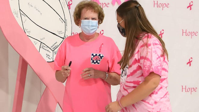 Vickie Webb, left, talks with Chelsea Pearcy, before signing the breast cancer survivor HOPE display Tuesday, Oct. 13, 2020, at H.B. Stewart Arena during Greenwood's Pink-Out volleyball game against Siloam Springs.