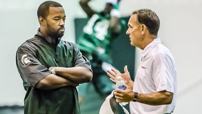 Coach Mark Dantonio, right, speaks with Curtis Blackwell