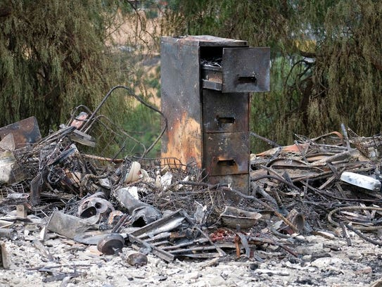 The charred remains of a burned out home are seen Monday,