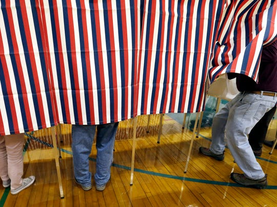 """FILE - In this Nov. 8, 2016 file photo, a voter enters a booth at a polling place in Exeter, N.H. Tweets alone don't make it true. Donald Trump won the presidency earlier this month even as he lost the popular vote to Democrat Hillary Clinton, according to The Associated Press's vote-counting operation and election experts. Trump nonetheless tweeted on Nov. 26 that he won the popular vote. and alleged there was """"serious voter fraud"""" in California, New Hampshire and Virginia. There's no evidence to back up those claims."""