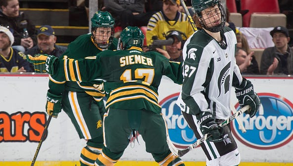 MSU freshman forward Mason Appleton (27) skates away as Northern Michigan's Dominik Shine, left, and John Siemer (17) celebrate a third-period, game-tying goal during the consolation game of the Great Lakes Invitational on Dec. 30 in Detroit. The Spartans lost 2-1 to the Wildcats in overtime.