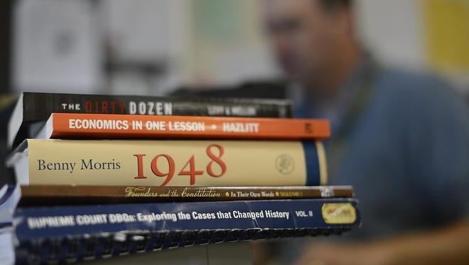 A stack of books inside Jeff Kline's classroom at Green Bay Preble High School. Kline teaches high school social studies.