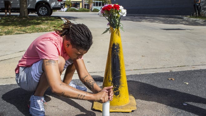 An unidentified woman lights a candle at a makeshift memorial to Jeremy McDole, shot and killed by Wilmington police at Tulip and Scott streets on Wednesday. The Delaware Black Caucus is calling for an independent federal investigation into the shooting.