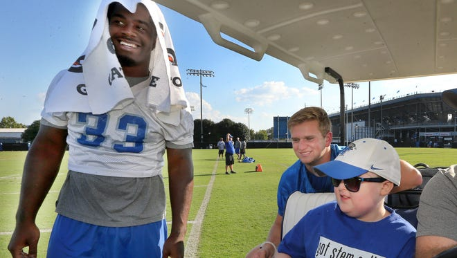 MTSU's Myles Harges (33) talks with Colton Sheets a young cancer survivor as he tours practice on Thursday, Sept. 22, 2016. MTSU kicker Canon Rooker (15) rides around practice with Colton, who will be MTSU's honorary Captain for the home game against Louisiana Tech, Saturday.