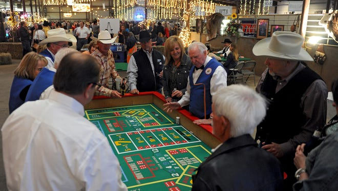 Times Record News File PhotoA group gathers around the craps table in the gaming and casino area of the 2014 Cattle Baron's Ball at the J.S. Bridwell Agricultral Center.