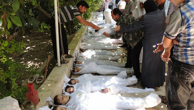 Syrian citizens try to identify dead bodies, after an alleged poisonous gas attack fired by regime forces.