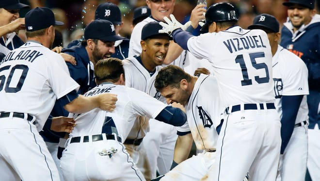 Tigers second baseman Ian Kinsler is surrounded by teammates after hitting a walk-off home run to defeat the Royals, 6-5, in the 11th inning Saturday at Comerica Park.