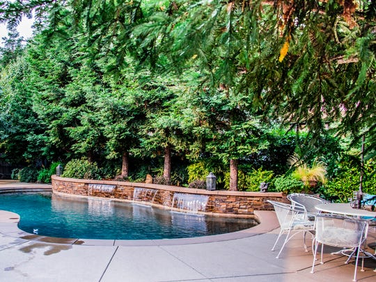 The backyard of the Lollar home is an oasis featuring a pool and lush landscaping.