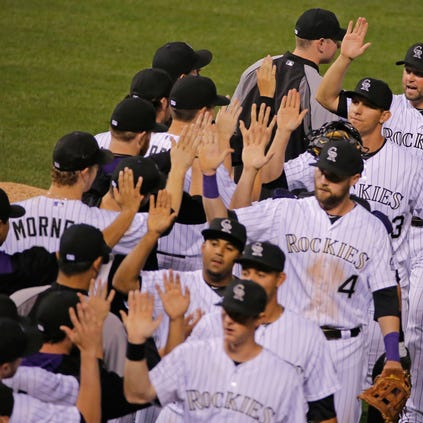 DENVER, CO - SEPTEMBER 19:  Michael Cuddyer #3 of the Colorado Rockies and his teammates celebrate their 15-3 victory over the Arizona Diamondbacks at Coors Field on September 19, 2014 in Denver, Colorado.  (Photo by Doug Pensinger/Getty Images)