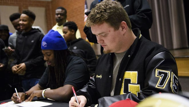 Greer High seniors Travigea Ware, left, and Bradly Thompson sign with Presbyterian College and South Carolina State, respectively, Wednesday, in the school's auditorium.