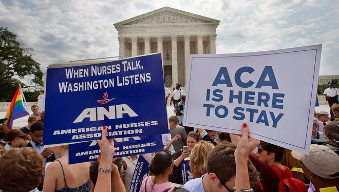 Supporters of the Affordable Care Act hold up signs as the opinion for health care is reported outside of the Supreme Court in Washington, Thursday June 25, 2015. The Supreme Court on Thursday upheld the nationwide tax subsidies under President Barack Obama's health care overhaul, in a ruling that preserves health insurance for millions of Americans. The justices said in a 6-3 ruling that the subsidies that 8.7 million people currently receive to make insurance affordable do not depend on where they live, under the 2010 health care law.