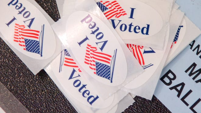 'I voted' stickers rest on a ballot box.