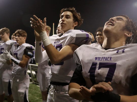 Shasta High School football team members Dakota Mosby, from right, Ian Garcia, and other members of the team sing their fight song to their fans Saturday after the Wolves 41-6 loss to Bishop Diego.