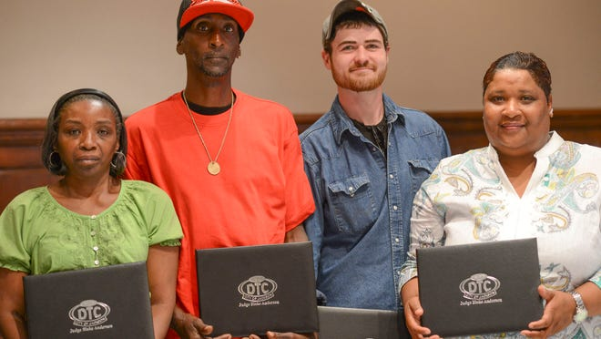 Graduates of the City of Jackson Drug Treatment Court hold their diplomas at Jackson City Hall Wednesday morning after graduating.