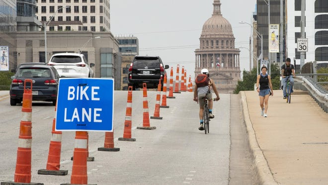 A cyclist uses a temporary bicycle lane on Congress Avenue on July 6.  Austin's Transportation Department had installed protected bicycle lanes on Congress Avenue from Riverside Drive to 11th Street to help cyclists and pedestrians maintain physical distancing during the coronvirus pandemic.