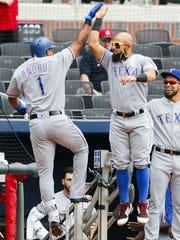 Texas Rangers' Elvis Andrus (1) celebrates his home run with Rougned Odor (12) in the first inning of the first game of a baseball doubleheader against the Atlanta Braves, Wednesday, Sep. 6, 2017, in Atlanta.
