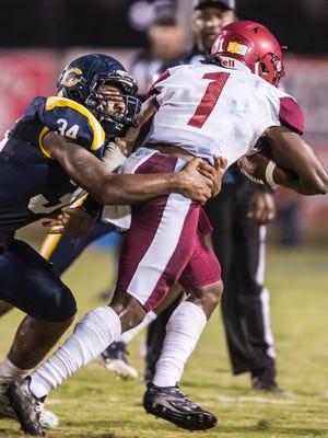 Carencro's Jalen Angelle (34) sacks the Ouachita Parish Lions quarterback Friday Sept. 22, 2017.