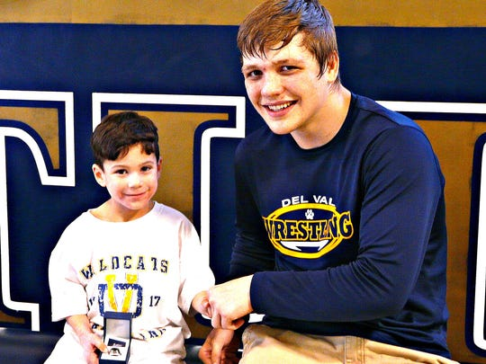 Delaware Valley High School standout Kyle Lightner, who wrestled at 195 pounds, received his championship ring from Finn Dobak, 5, a 32-pounder who wrestles with the Wildcats.