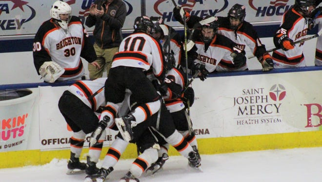 Brighton's Will Jentz (10) jumps on the celebration pile after Brighton's first goal was scored by Adam Conquest to give the Bulldogs a first-period 1-0 lead.