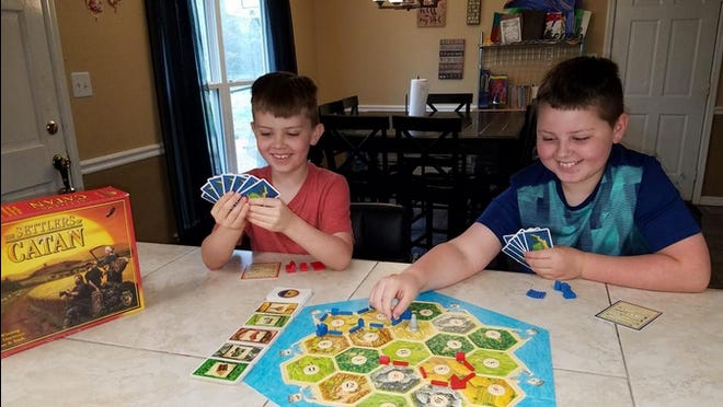 "James and Braeden Will play the board game ""Settlers of Catan"" at their home."