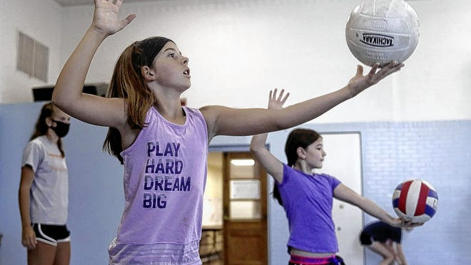 Emma Jahn, foreground, 10, and Avery Potts, 9, practice serving the ball June 25 as part of a four-day youth volleyball clinic through Grove City Parks and Recreation at the Kingston Center in Grove City. Some programming is getting underway while some summer staples will not be held this year due to the COVID-19 coronavirus pandemic.
