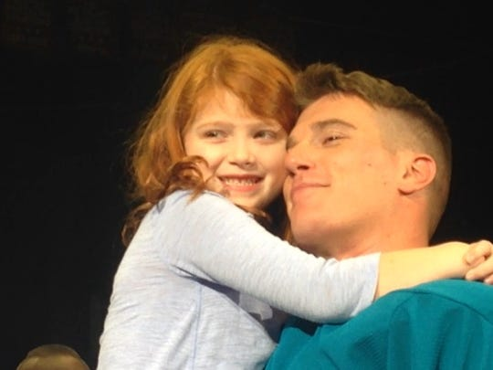 Sgt. Jesse Fuller hugs daughter Ella, 6, after surprising his family at a Knighthawks game on Dec. 12, 2015.