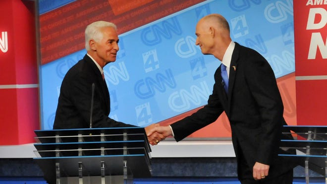 Democratic candidate Charlie Crist, left, and Republican Gov. Rick Scott shake hands before their live television debate, Tuesday, Oct. 21, 2014 hosted by WJXT-TV and CNN at the Channel 4 studios in Jacksonville, Fla. (AP Photo/The Florida Times-Union, Will Dickey, Pool)