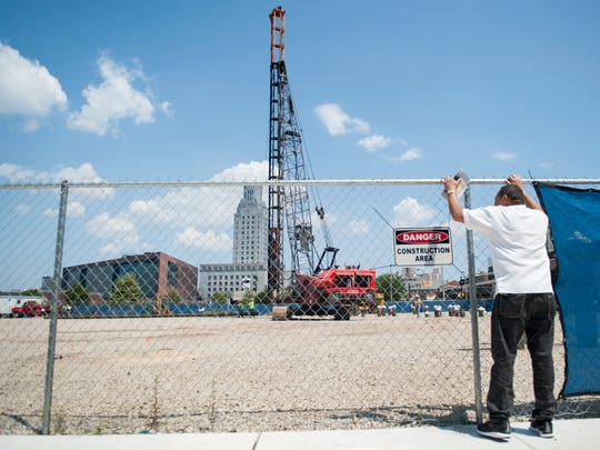 Camden resident Dario Aldama watches as a pile driver pounds a steel tube into the ground at the construction site of the Joint Health Sciences Center in downtown Camden.  08.01.17