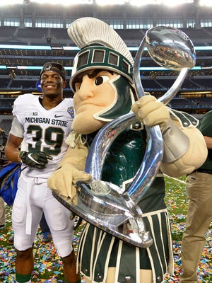 Jermaine Edmondson and Sparty pose with the Cotton Bowl trophy at the end of last season.