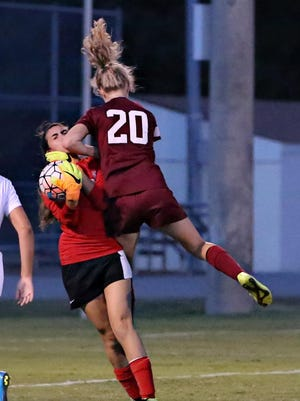 USJ's Morgan Williams gets an elbow to the face from a St. George's player, but she still holds onto the ball to prevent a goal.