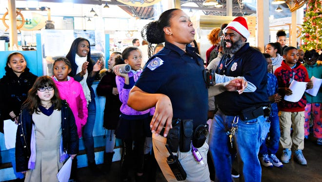 York City School Police Officer Britney Brooks, front left, and Chief Mike Muldrow, front right, lead York City School students as they sing carols to spread holiday cheer at Central Market in York City, Tuesday, Dec. 19, 2017. Dawn J. Sagert photo