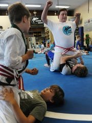"""Jonny Lipnicki, upper right, on his back facing assistant instructor Ryan Barber, is a brown belt in Brazilian jiujitsu.  Lipnicki, who was in """"Jerry Maguire,"""" graduated from Agoura High School and is shown giving a demonstration  Lacombe Martial Arts in Westlake Village. Max Chizzo, left, and Tommy Sherren practice the bump as Lipnicki demonstrates."""