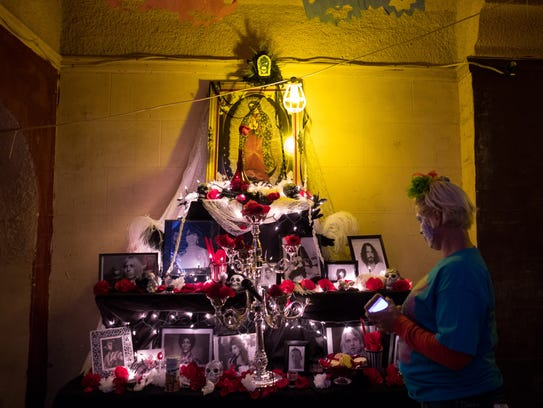 A woman looks at an altar in the Ritz Theater during