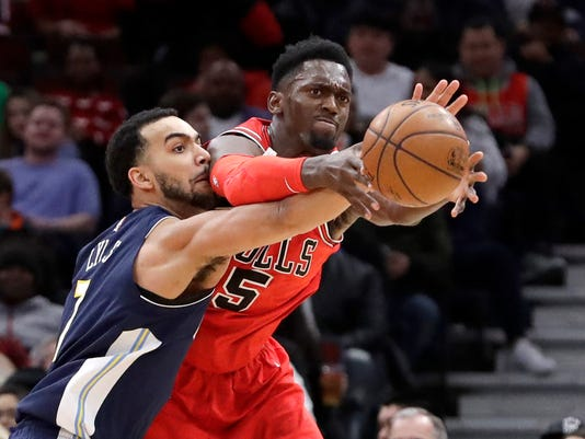 Denver Nuggets' Trey Lyles, left, knocks the ball away from Chicago Bulls' Bobby Portis during the first half of an NBA basketball game Wednesday, March 21, 2018, in Chicago. (AP Photo/Charles Rex Arbogast)