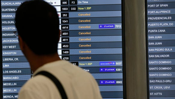 A traveler looks at a monitor listing canceled flights