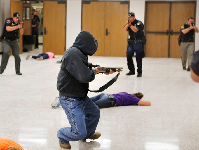 An armed man falls under a hail of gunfire from approaching police officers during a mock shooting demonstration as part of Active Shooter Training Thursday, August 7, 2014, at Clinton Prairie High School near Frankfort. In addition to the mock shooting demonstration, the training for police teachers, staff and others included presentations from law enforcement officers, and breakout sessions to  discuss scenarios and answer questions.