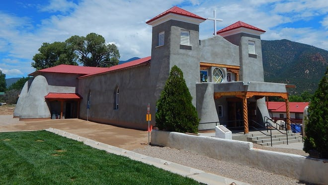 This Aug. 10, 2016, photo provided by Carrie Leven shows the exterior of the reconstructed San Antonio Catholic Church in Questa, N.M. The community will celebrate the rededication of the church with a special Mass on Sunday, Aug. 14, 2016. It took volunteers tens of thousands of hours over the last several years to rebuild the heart of one mountain village in northern New Mexico.