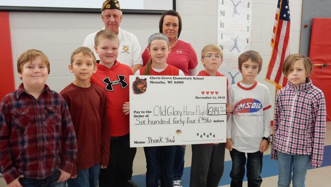 The Clovis Grove Elementary School Leadership Club presented a check for $644 to the VFW Nicolet Post 2126 Menasha Nov. 11. The students raised $322 and the PTO matched that amount. Nicolet Elementary also contributed $291. The Post will match the total donations. The money will be used to pay for Old Glory Honor Flights. Pictures are (first row, from left) Cameren Armstrong, Logan Higgins, Dylan Steenis, Madison Zaves, Chase Parker, Eli Minot and Jewlyana Raimer; (second row) Commander David Mix and Clovis PTO member Alicia Jackson.