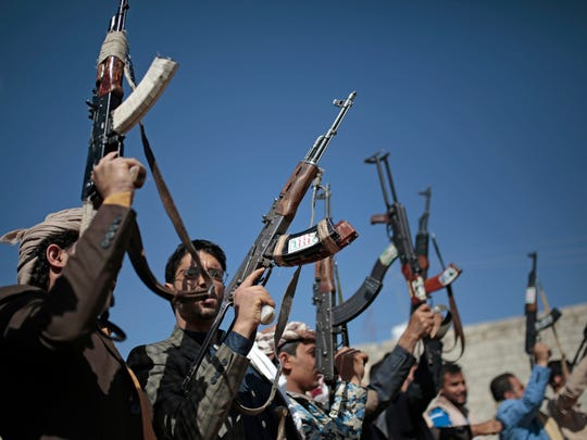 Tribesmen loyal to Houthi rebels hold up their weapons