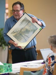 Mike Morris was among many who bought paintings Thursday at Plato Pavis' exhibit at HealthPark Medical Center in south Fort Myers. Pavis has volunteered at HealthPark since 2000 and is painting tiles for the healing ceilings project of Lee Memorial's arts in healthcare program.