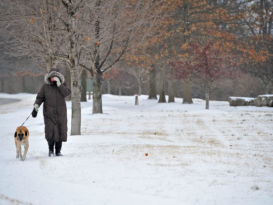 Kate Smith walks her dog Lucie in the snow along Carothers