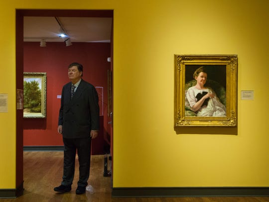 Gerret Copeland, who has given $15 million to the Delaware Art Museum, stands at the entrance to the American art wing, near a portrait of his grandmother, who founded the museum.