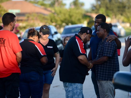 Miguel Cruz, of Port St. Lucie, prays with Remy Noel,