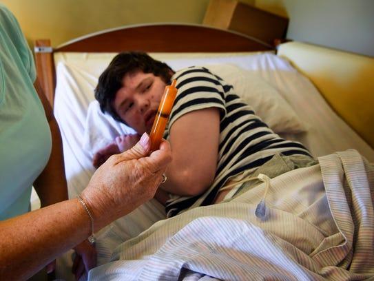 Michelle Sampson prepares seizure medication for her