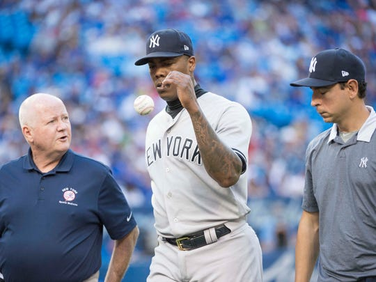 Jul 7, 2018; Toronto, Ontario, CAN; New York Yankees relief pitcher Aroldis Chapman (54) walks towards the dugout with head athletic trainer Steve Donohue, left, and interpreter Marlon Abreu, right, in the ninth inning against the Toronto Blue Jays at Rogers Centre.
