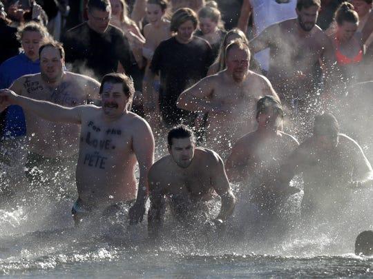 Participants in the annual Polar Bear Plunge run into