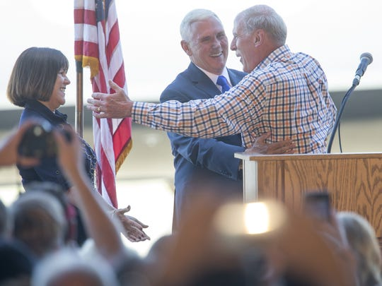 Karen Pence (left), her husband Mike Pence, and Dan Coats greet each other, as about 150 well-wishers turned out for the Pences at a homecoming rally at the Indianapolis Executive Airport for Pence on July 16, 2016.